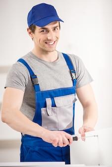 Glimlachende hersteller die binnenland van reparatiehulpmiddelen thuis gebruiken.
