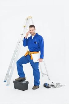 Glimlachende hersteller met toolbox en ladder die cellphone gebruiken