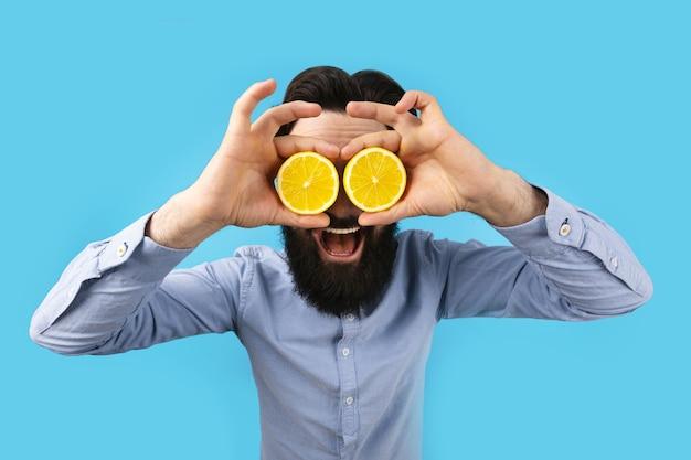 Glimlachende hipster man met plakjes citroen voor ogen, over blauwe muur, fruit en gezonde biologische voeding, citrusvitamine