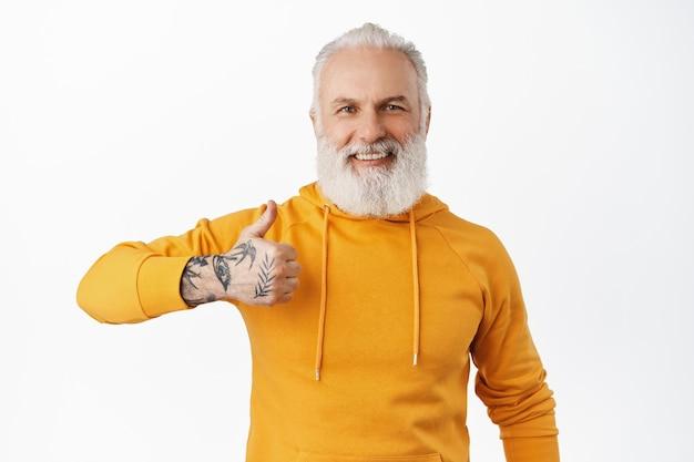 Glimlachende hipster oude man toont duim met zijn getatoeëerde hand, keurt iets goed en vindt het leuk, prijs uitstekend werk, complimenteert, zeg ja, witte muur