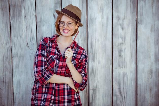 Glimlachende hipster vrouw die een potlood houdt,