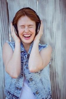 Glimlachende hipster vrouw die haar oren tot een kom vormt, luisterend aan luide muziek
