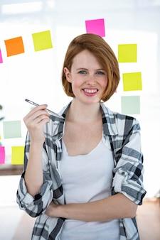 Glimlachende hipster vrouw, zittend aan haar bureau, met een pen in haar hand