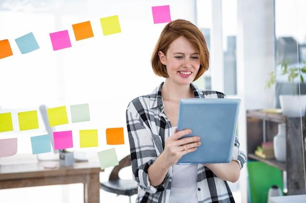 Glimlachende hipster vrouw, zittend aan haar bureau op haar taableet