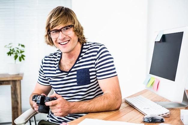 Glimlachende hipster zakenman die foto op camera in zijn bureau controleren