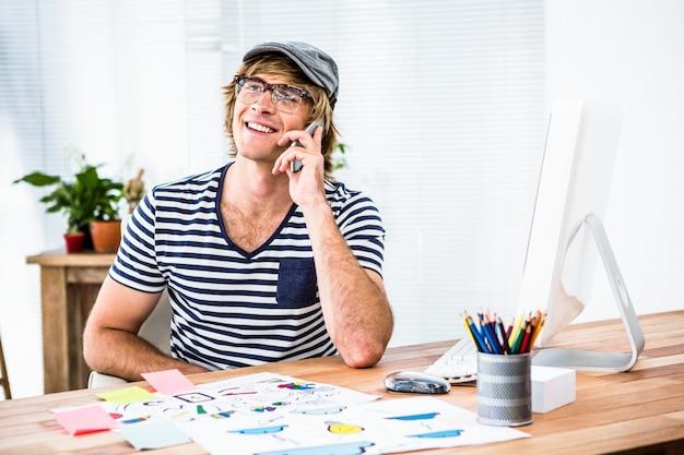 Glimlachende hipster zakenman die op de telefoon in zijn bureau spreekt