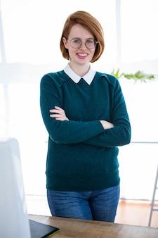 Glimlachende hipster zakenvrouw, staande in haar kantoor met haar armen over elkaar