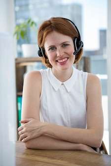 Glimlachende hipster zakenvrouw, zittend aan haar bureau in een draadloze headset