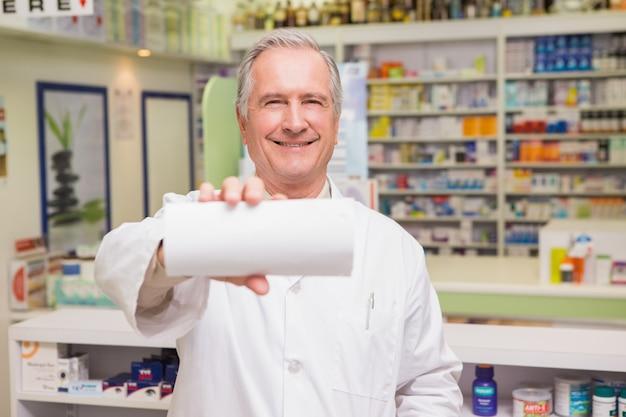 Glimlachende hogere apotheker die document toont