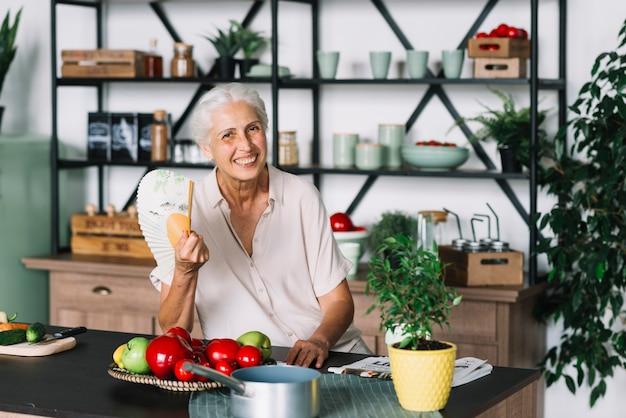Glimlachende hogere de ventilator in hand zitting van de vrouwenholding achter keukentop