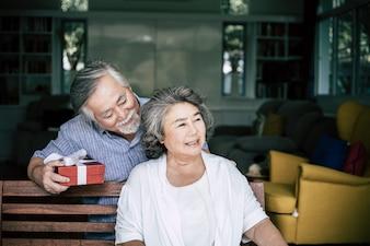 Glimlachende hogere echtgenoot die verrassing maken die doos tot zijn vrouw geven