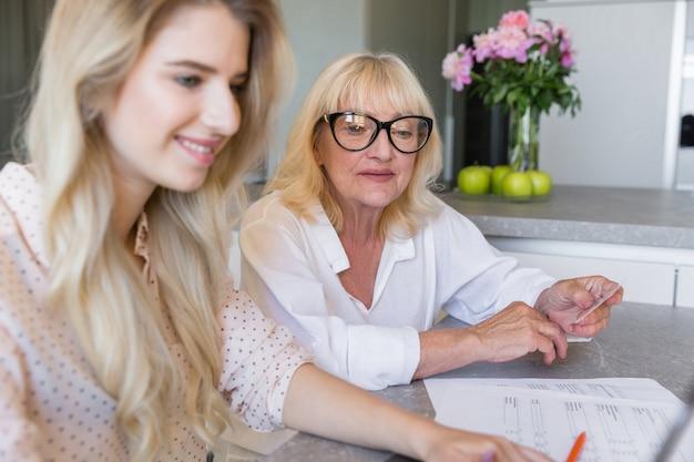 Glimlachende hogere grootmoeder met haar kleindochter die online betaalt