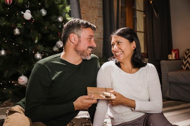 Glimlachende hogere mens die een gift geeft aan zijn echtgenoot
