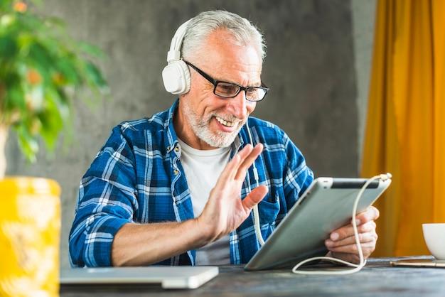 Glimlachende hogere mens die hello op digitale tablet zegt