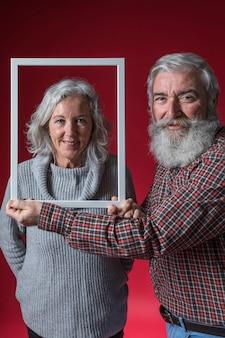 Glimlachende hogere mens die witte kadergrens voor het gezicht van zijn vrouw houden tegen rode achtergrond