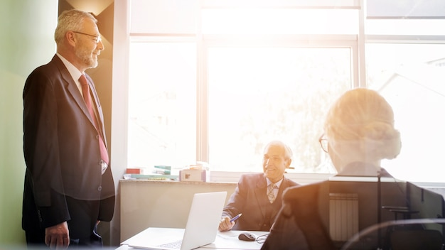 Glimlachende hogere mens die zijn medewerker bekijkt die in het bureau werkt
