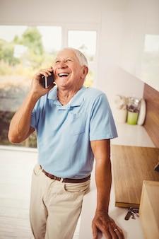 Glimlachende hogere mens op een telefoongesprek in de keuken