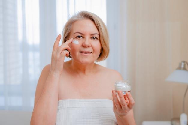 Glimlachende hogere vrouw die anti-veroudert lotion toepast om donkere kringen onder ogen te verwijderen.