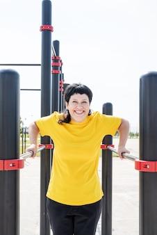 Glimlachende hogere vrouw die omgekeerde push-ups buiten op de sportveldbalken doet