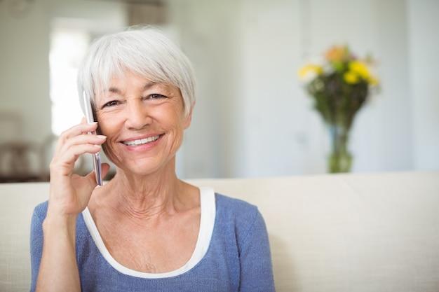 Glimlachende hogere vrouw die op mobiele telefoon in woonkamer spreekt