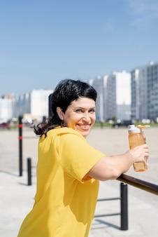 Glimlachende hogere vrouw die rust na training buiten op de bars van het sportveld heeft