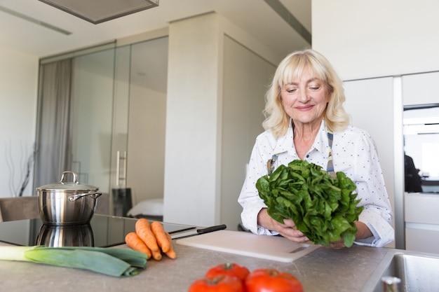 Glimlachende hogere vrouw die salade voorbereidt bij de keuken