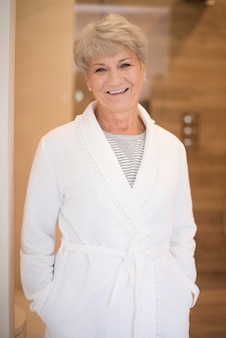 Glimlachende hogere vrouw in de badjas