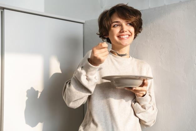 Glimlachende hongerige jonge vrouw die zich bij de koelkast bevindt, die pap eet