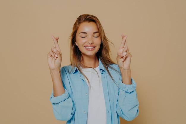 Glimlachende hoopvolle jonge vrouw met gesloten ogen en gekruiste vingers aan beide handen die hoop en geloof in een betere toekomst demonstreren, glimlachend terwijl ze poseren geïsoleerd op beige achtergrond
