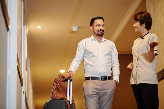 Glimlachende hotelconciërge helpt gasten met bagage om kamer te vinden