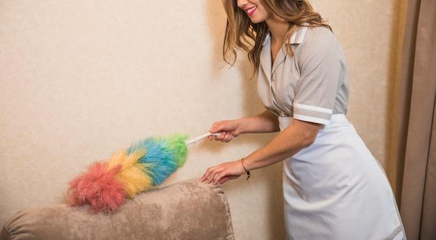 Glimlachende huishoudster die de bank met kleurrijke stofdoek schoonmaken