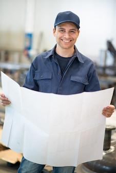 Glimlachende ingenieur die een bluepringtekening leest in een industriële faciliteit