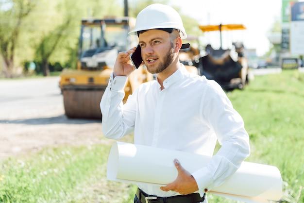 Glimlachende ingenieur met helm die zich voor graafwerktuig op de bouwplaats van de weg bevindt