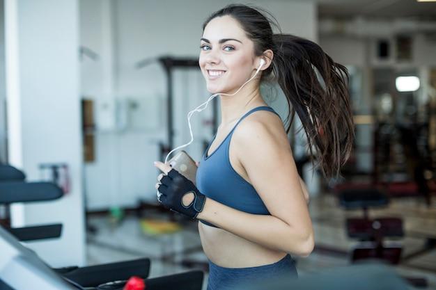 Glimlachende joggingvrouw die aan muziek luistert