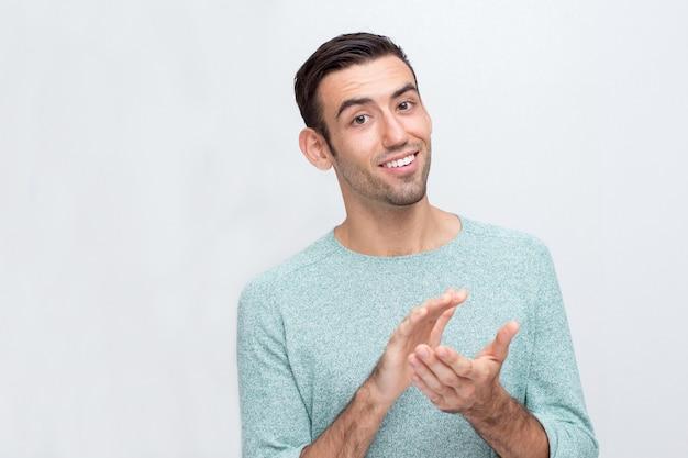 Glimlachende jonge aantrekkelijke man klapende handen