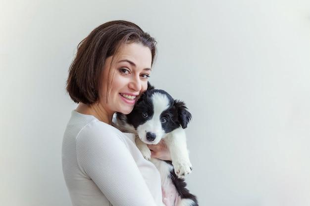 Glimlachende jonge aantrekkelijke vrouw die leuke border collie van de puppyhond omhelzen die op wit wordt geïsoleerd
