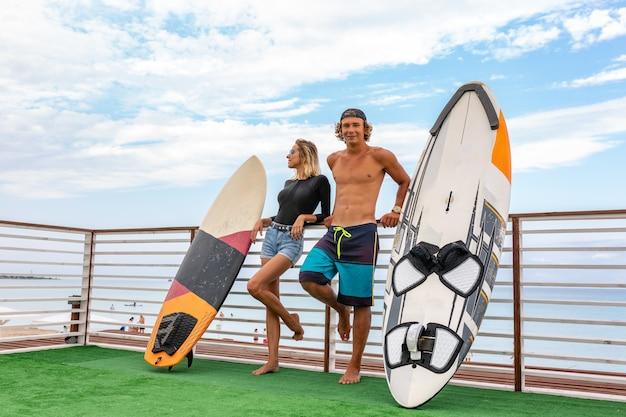 Glimlachende jonge actieve paarsurfers die op het strand na sport met surfplank ontspannen. gezonde levensstijl. extreme watersporten