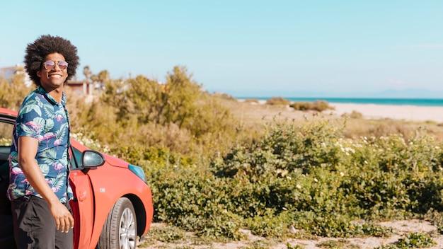 Glimlachende jonge afrikaanse amerikaanse mens die zich dichtbij auto op strand bevindt