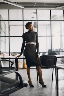Glimlachende jonge afrikaanse amerikaanse onderneemster die in een bureau werkt. bedrijfsconcept.
