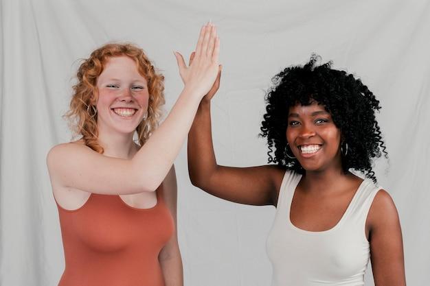 Glimlachende jonge afrikaanse en blonde vrouwen die hoogte vijf geven tegen grijze achtergrond
