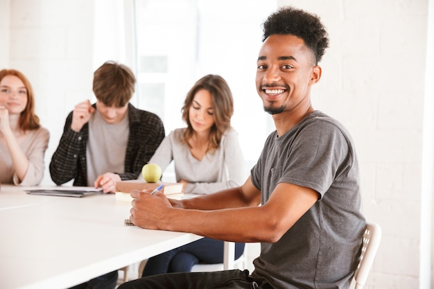 Glimlachende jonge afrikaanse kerel in klaslokaal