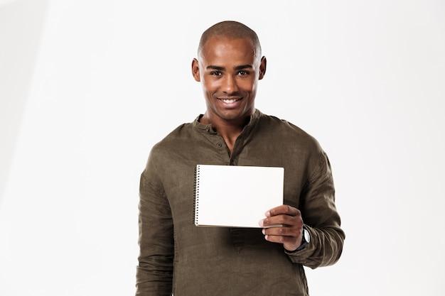 Glimlachende jonge afrikaanse mens die notitieboekje toont.