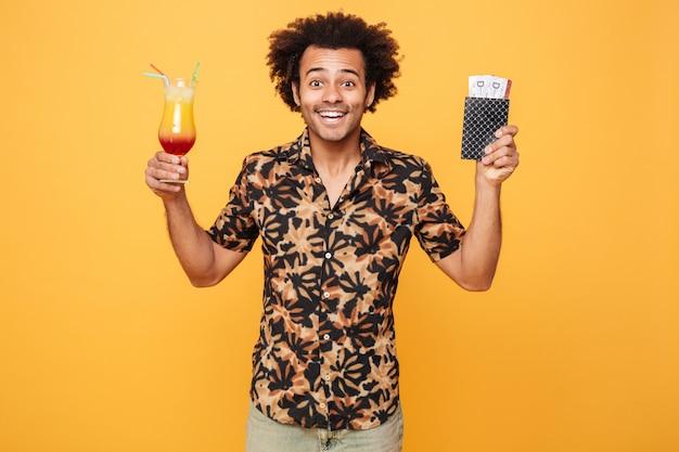Glimlachende jonge afrikaanse mens het drinken cocktail en het houden van kaartjes.
