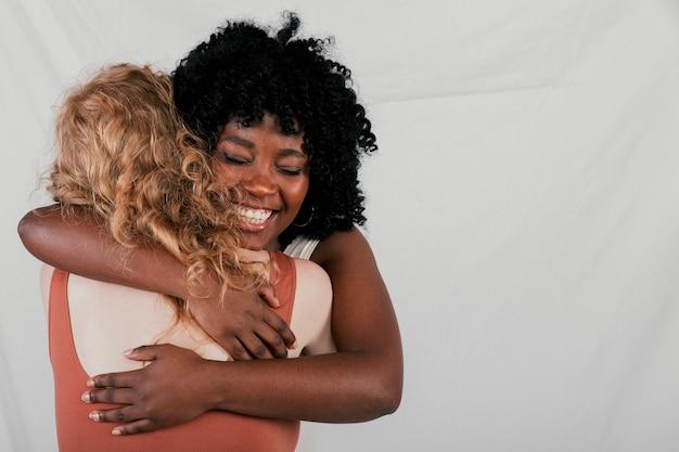 Glimlachende jonge afrikaanse vrouw die haar kaukasische vrouwelijke vriend koesteren tegen grijze achtergrond