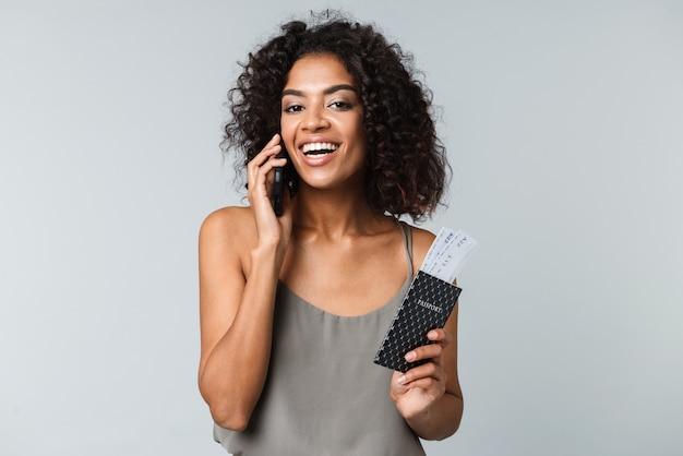 Glimlachende jonge afrikaanse vrouw die zich geïsoleerd bevindt, vliegtickets met paspoort toont, die op mobiele telefoon spreekt