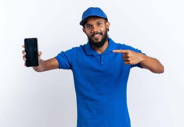 Glimlachende jonge afro-amerikaanse bezorger die vasthoudt en naar de telefoon wijst die op een witte achtergrond met kopieerruimte wordt geïsoleerd