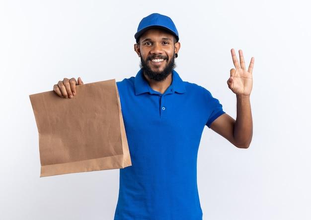 Glimlachende jonge afro-amerikaanse bezorger die voedselpakket vasthoudt en gebaren ok teken geïsoleerd op een witte achtergrond met kopie ruimte
