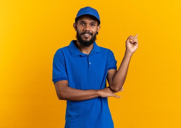 Glimlachende jonge afro-amerikaanse bezorger wijzend naar de zijkant geïsoleerd op een oranje achtergrond met kopieerruimte