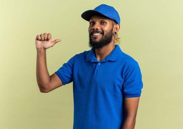 Glimlachende jonge afro-amerikaanse bezorger wijzend naar zichzelf geïsoleerd op olijfgroene achtergrond met kopieerruimte