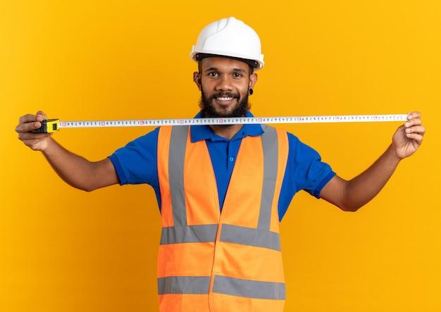 Glimlachende jonge afro-amerikaanse bouwer man in uniform met veiligheidshelm met meetlint geïsoleerd op een oranje achtergrond met kopie ruimte
